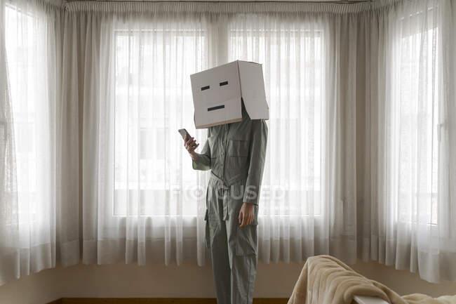 Donna che indossa una scatola di cartone in testa con il viso utilizzando smartphone a casa — Foto stock