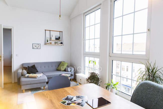 Фотографии и планшет на столе в светлой гостиной с большими окнами — стоковое фото