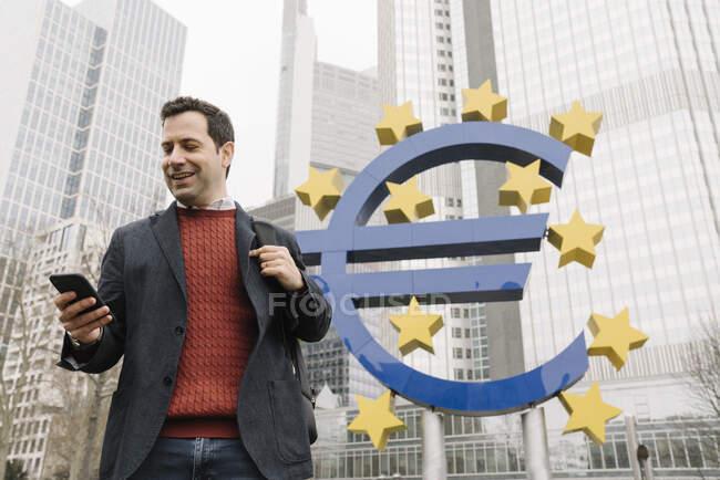 Uomo d'affari sorridente utilizzando il telefono cellulare mentre in piedi contro scultura e Banca centrale europea — Foto stock