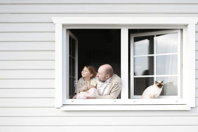 Homem maduro com sorridente filha e gato inclinado para fora da janela de sua casa — Fotografia de Stock