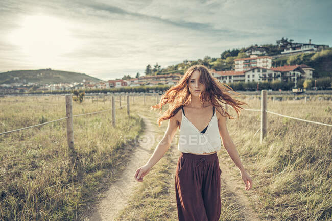 Red-haired woman walking on a path and rotating — Stock Photo