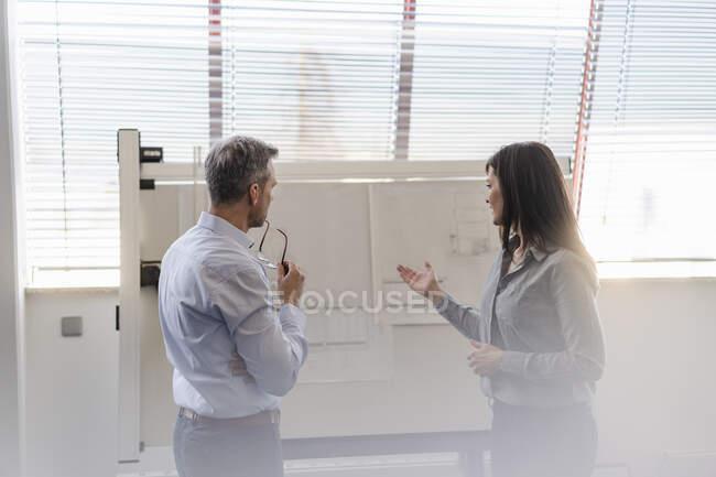 Empresario y empresaria teniendo una reunión en el cargo - foto de stock