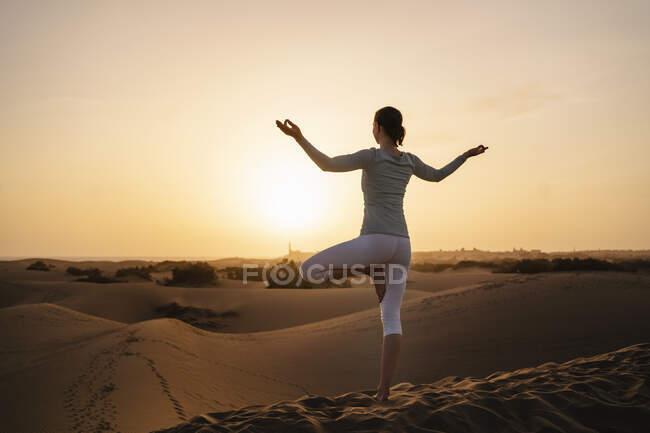 Женщина, практикующая йогу в песчаных дюнах на закате, Гран-Канария, Испания — стоковое фото