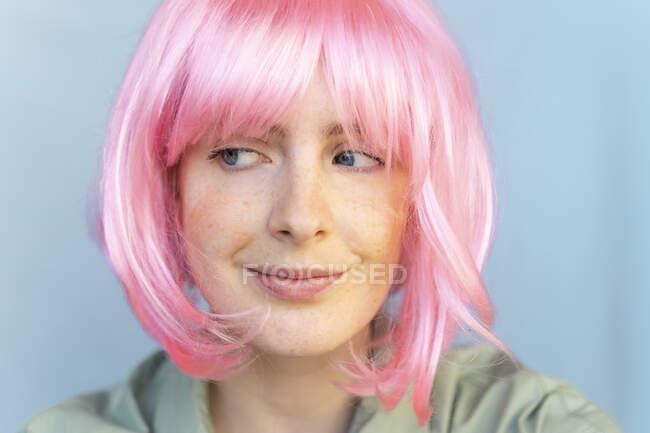 Retrato de mujer joven con peluca rosa mirando hacia los lados - foto de stock