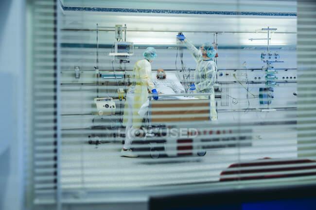 Médicos por trás do cuidado às cegas solares do paciente em uma unidade de emergência de um hospital com equipamentos respiratórios — Fotografia de Stock