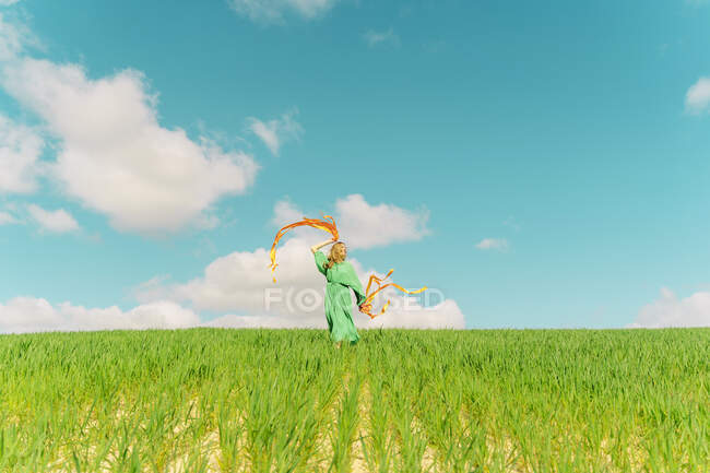 Young woman wearing a green dress moving in a field with ribbons — Stock Photo
