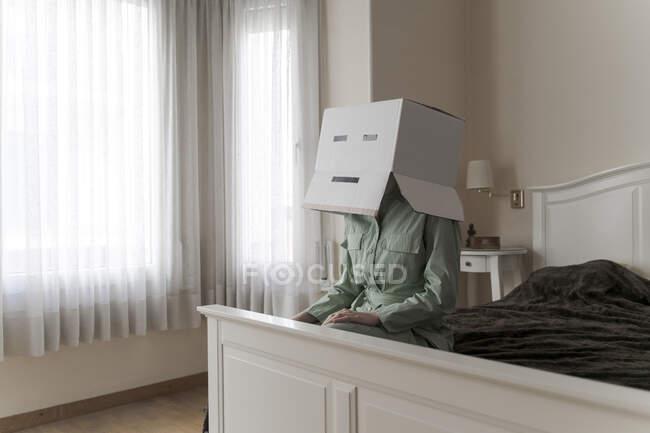 Donna che indossa una scatola di cartone sulla testa con sorriso annoiato seduta sul letto — Foto stock