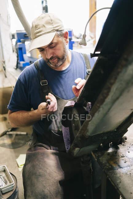 Artesanato fazendo facas em sua oficina examinando a lâmina — Fotografia de Stock