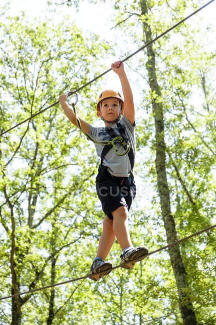 Мальчик на верёвке в лесу — стоковое фото