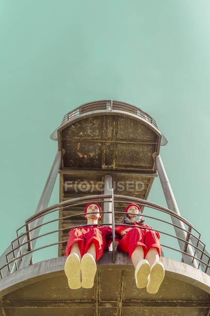 Pareja joven vestida con monos rojos y sombreros sentados uno al lado del otro en la plataforma mirando a la distancia - foto de stock