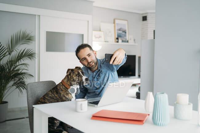 Homem adulto médio tomando selfie com o cão enquanto trabalhava em casa durante a crise do coronavírus, Almeria, Espanha, Europa — Fotografia de Stock