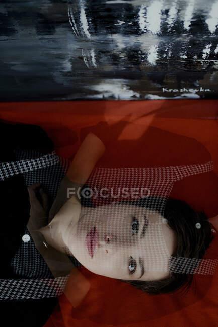 Retrato de una mujer de pelo corto acostada junto a la pintura - foto de stock