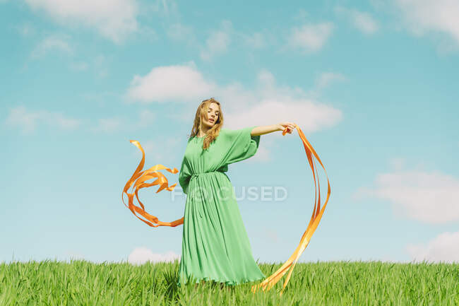 Молодая женщина в зеленом платье, стоящая в поле с развевающимися лентами — стоковое фото