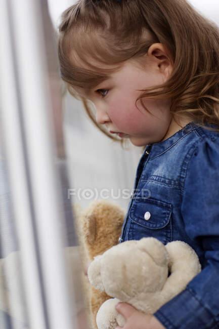 Perfil de niña seria con osos de peluche - foto de stock
