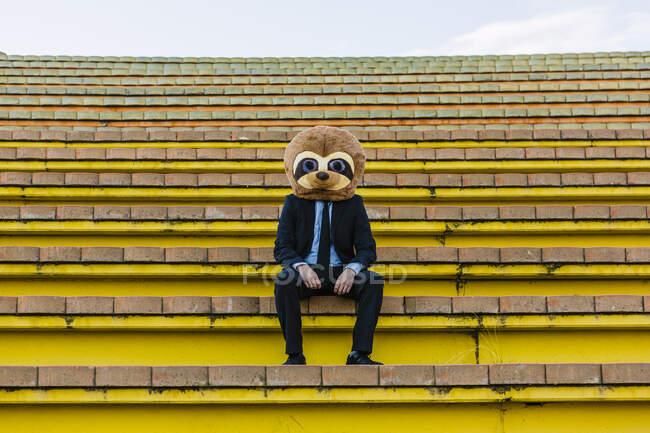 Empresario en traje negro con máscara de suricata sentado en las escaleras - foto de stock
