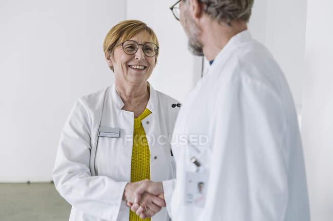 Dos doctores sonrientes dándose la mano - foto de stock