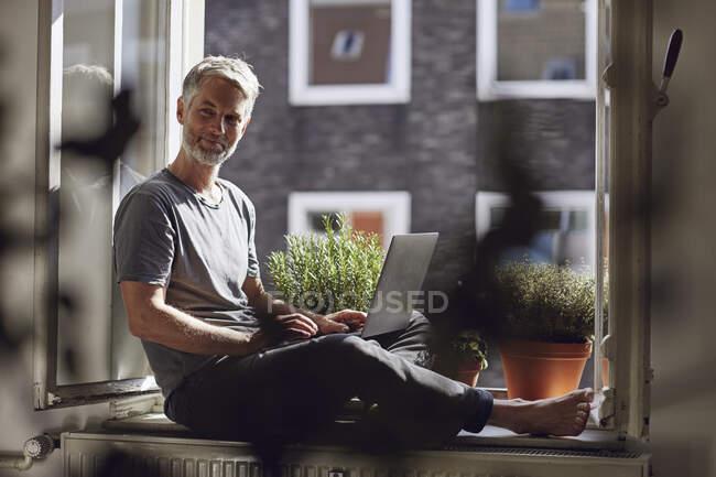 Зрелый мужчина сидит у окна дома с ноутбуком — стоковое фото