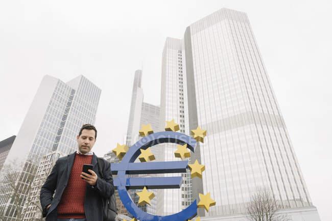 Vista a basso angolo dell'uomo d'affari che utilizza il telefono cellulare contro il simbolo dell'euro e la Banca centrale europea a Francoforte, Germania — Foto stock