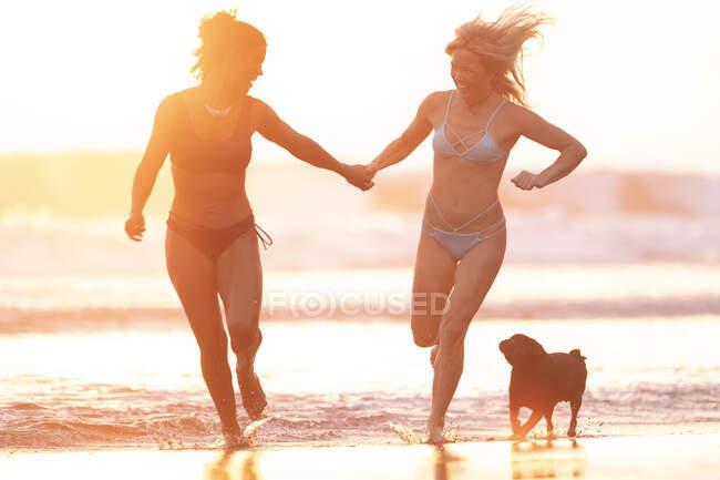 Dos mujeres felices corriendo en la playa al atardecer, Costa Rica - foto de stock