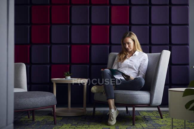 Женщина, сидящая в кресле в современном журнале для чтения — стоковое фото