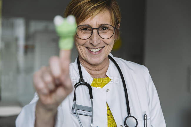Retrato de médico feliz con muñeca de dedo - foto de stock