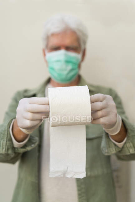Homem com máscara facial e luvas de proteção, segurando rolo de papel higiênico — Fotografia de Stock