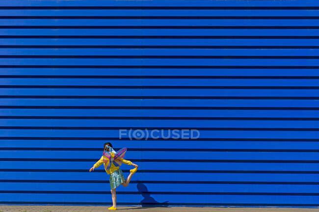 Vista posterior de la niña con alas de mariposa de colores equilibrándose en una pierna delante de fondo azul - foto de stock
