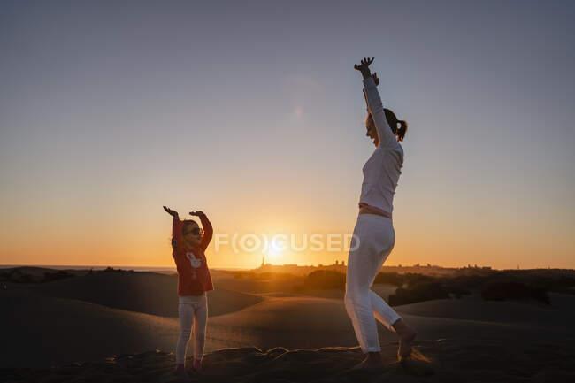 Feliz madre e hija en dunas de arena al atardecer, Gran Canaria, España - foto de stock