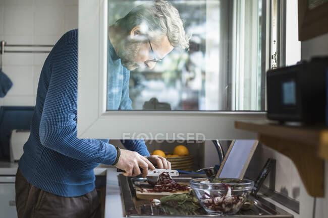 Hombre maduro preparando ensalada en ventana abierta en su cocina - foto de stock