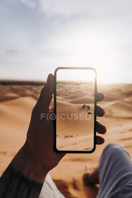 Ручной смартфон с фотографией пустыни — стоковое фото