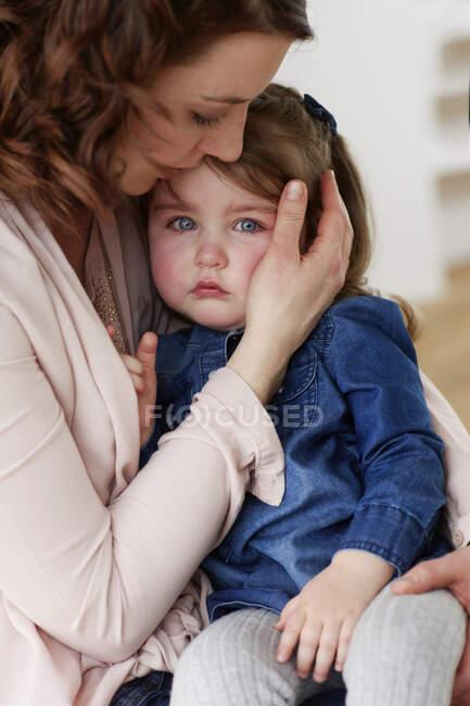 Joven madre consolando a su hijita - foto de stock