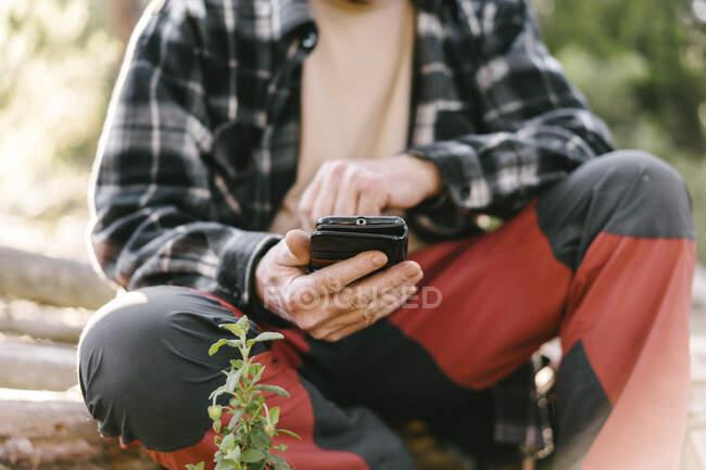 Ritaglia la vista dell'escursionista che ha una pausa usando il telefono cellulare — Foto stock