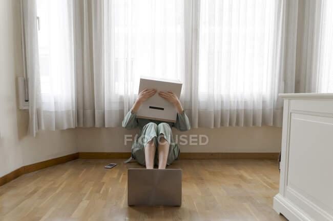 Mujer con una caja de cartón en la cabeza con sonrisa aburrida sentada en el suelo delante de la computadora portátil, cubriendo los ojos - foto de stock