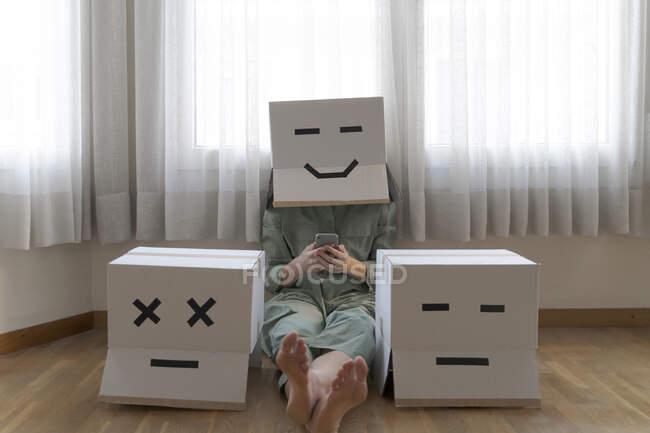 Donna che indossa una scatola di cartone con sorriso sorridente e seduta tra diverse scatole di cartone a casa e utilizzando smartphone, sorridente e scatola di cartone annoiata — Foto stock
