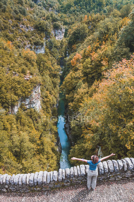 Spagna, Provincia di Huesca, Veduta aerea di una giovane donna in piedi con le braccia alzate sul ponte di pietra — Foto stock