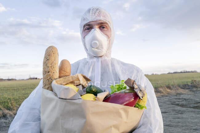 Retrato del hombre con traje protector y máscara sosteniendo bolsa de comestibles en el campo - foto de stock