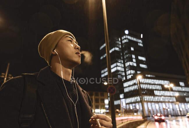 Elegante hombre con sombrero amarillo y auriculares fumando un cigarrillo en la ciudad por la noche - foto de stock