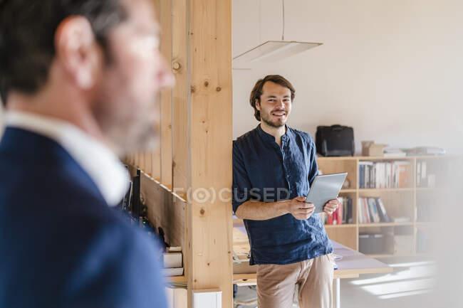 Homme d'affaires souriant tenant une tablette dans un bureau décloisonné en bois — Photo de stock