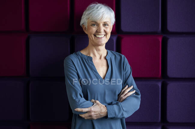 Portrait of happy senior woman with arms crossed — Stock Photo
