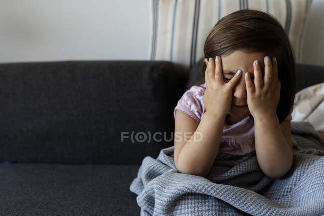 Retrato de niña sentada en el sofá con la cara oscura en casa - foto de stock