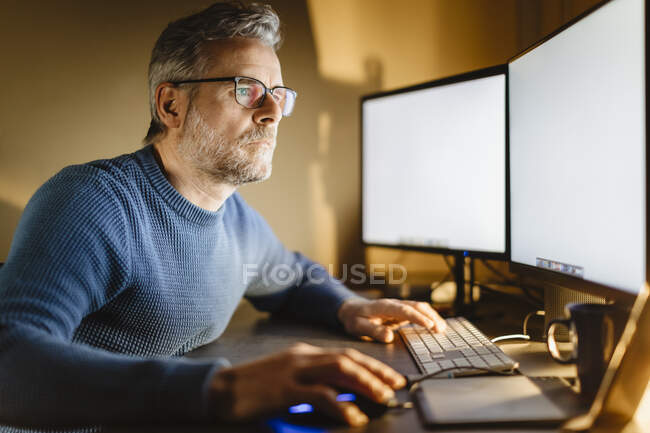 Mature man sitting at desk at home working on computer — Stock Photo