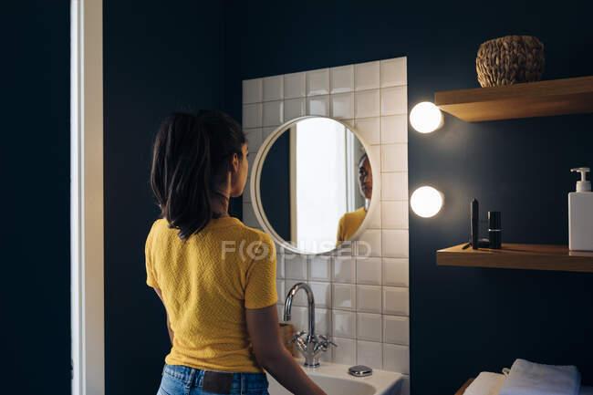 Молода жінка дивиться у дзеркало ванної кімнати. — стокове фото