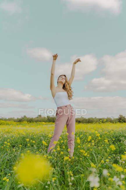 Девушка, стоящая на цветочном лугу весной — стоковое фото