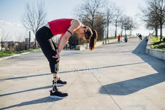 Уставшая спортивная девушка с протезом ноги, стоящая на дорожке — стоковое фото