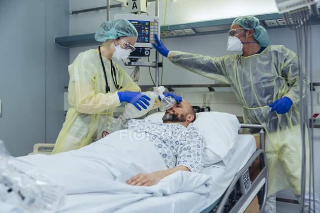 Médicos com máscara de válvula de bolsa que cuidam do paciente em unidade de pronto atendimento de um hospital — Fotografia de Stock