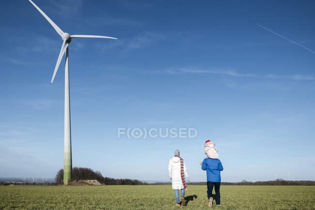 Visão traseira dos pais com a filhinha andando em um campo com roda de vento no fundo — Fotografia de Stock