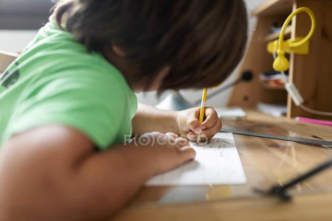 Boy doing his homework, sitting at desk — Stock Photo