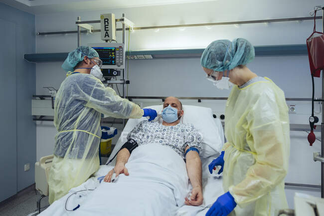 Médicos que cuidam do paciente em uma unidade de emergência de um hospital tomando temperatura — Fotografia de Stock