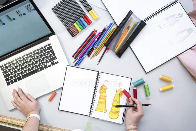 Costurera usando el ordenador portátil y el diseño de un vestido, vista desde arriba - foto de stock