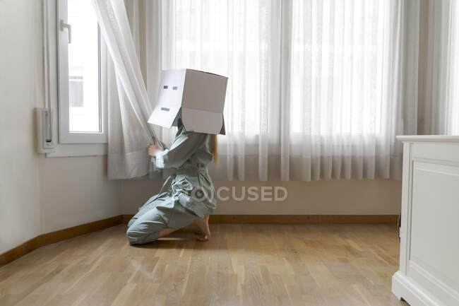 Donna che indossa una scatola di cartone in testa con sorriso annoiato guardando fuori dalla finestra — Foto stock